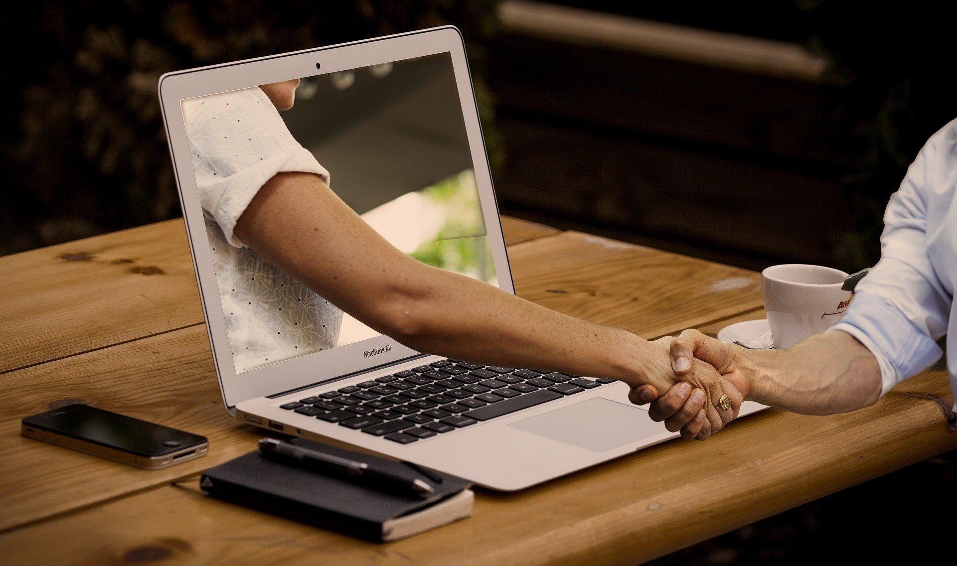 2 Menschen geben sich die Hand . Eine HAnd kommt aus dem Notebookbildschirm heraus.